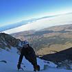 Posando para la foto, con un poco de polvo de la ventisca. Al fondo la sombra del coloso y el horizonte hacia el oeste. Foto: Ricardo Constante.